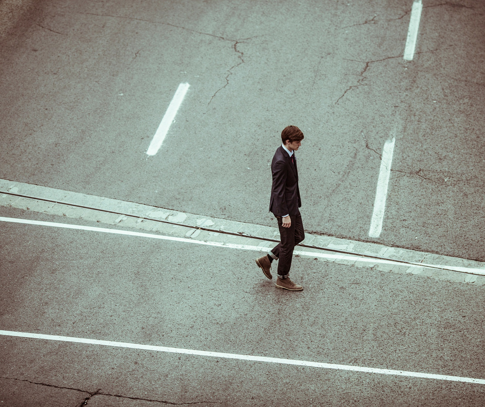 A businessman walks alone across a road