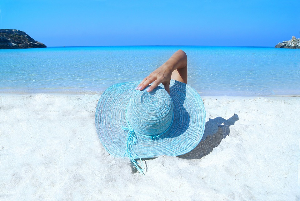 Lady in a blue straw hat lays on a beach looking out to sea