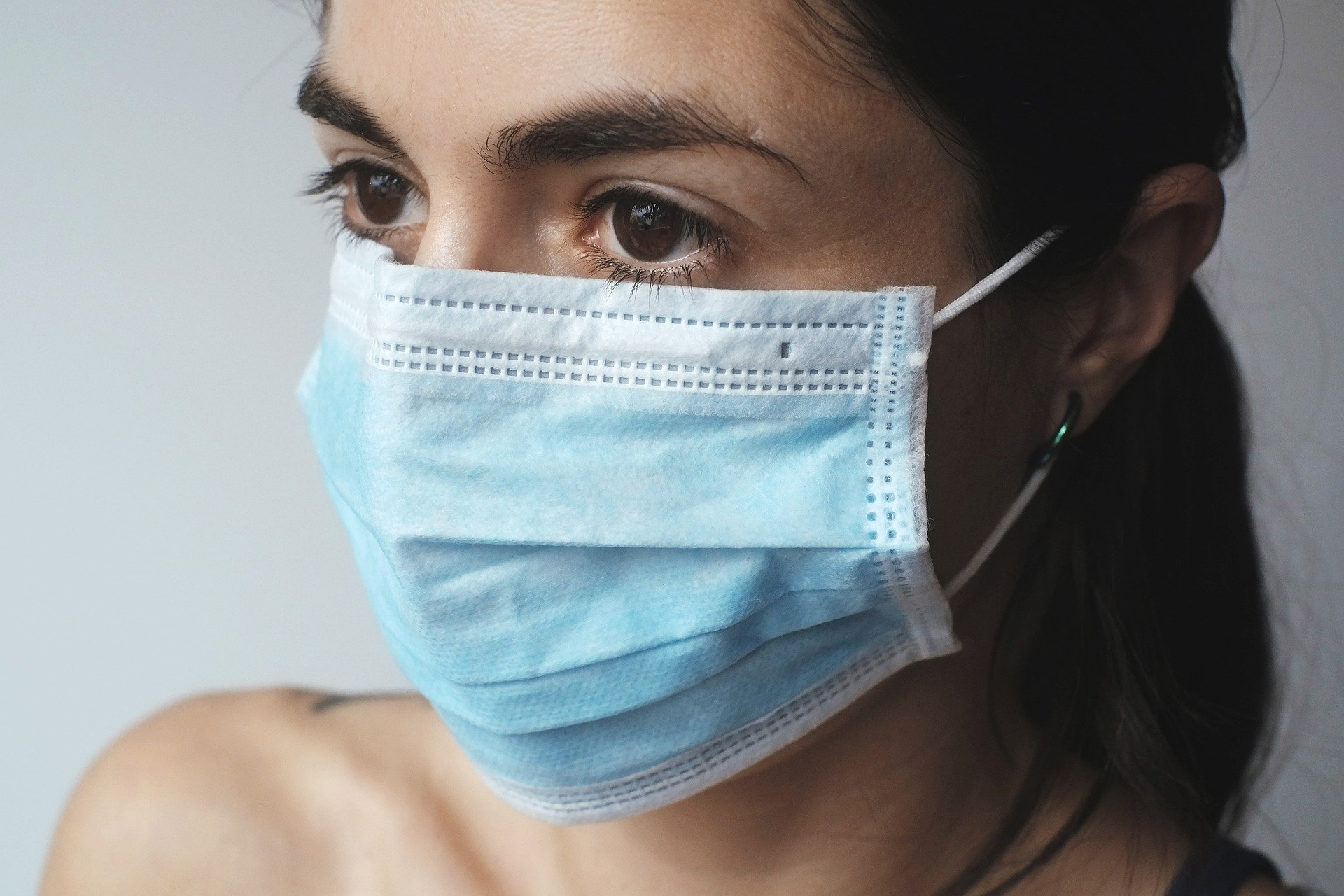 A woman wears a surgical face mask