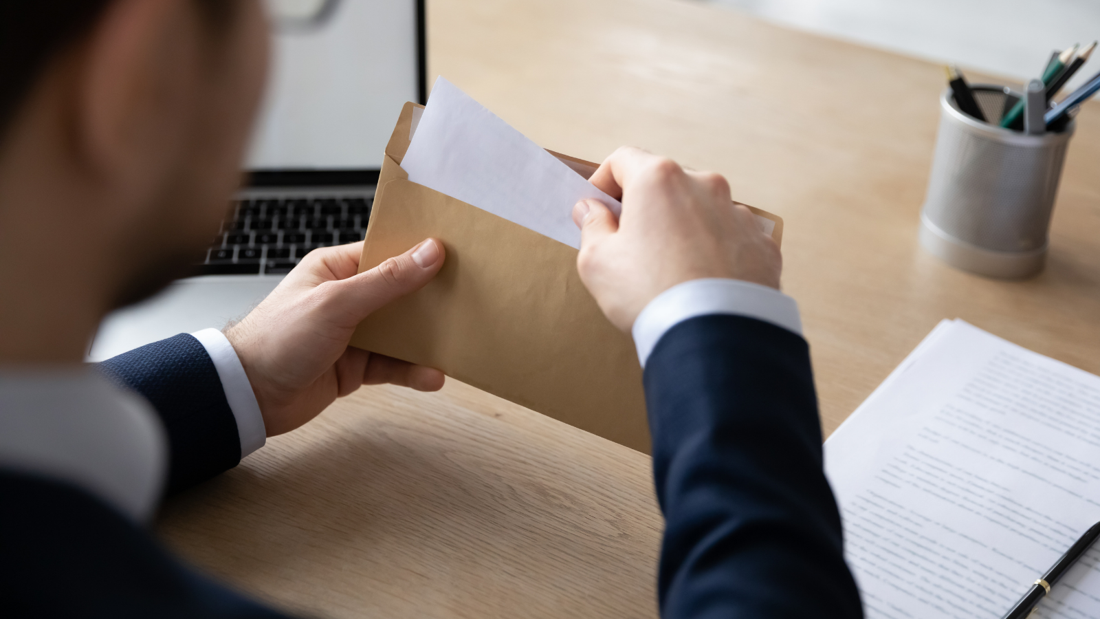 man opening a letter containing a reference
